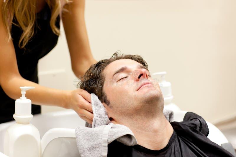 女性美发师他的人放松shampooed 免版税图库摄影
