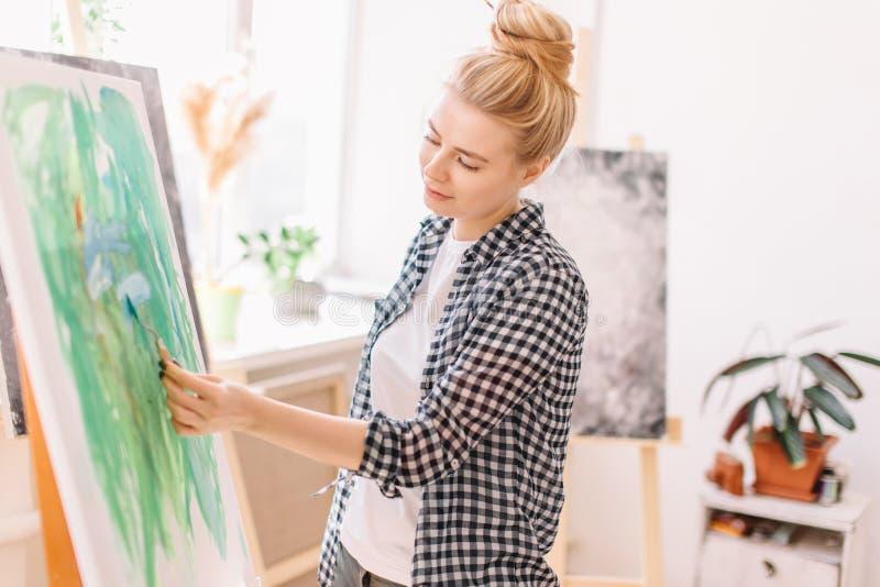 女性美好的艺术家绘画图片,使用小铲在车间 图库摄影