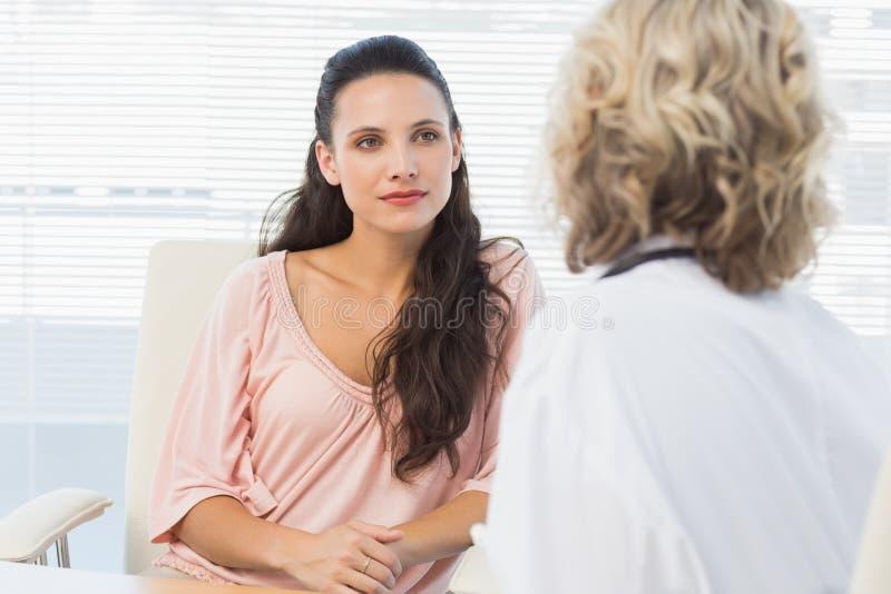 女性耐心听有集中的医生在医疗办公室 免版税库存照片