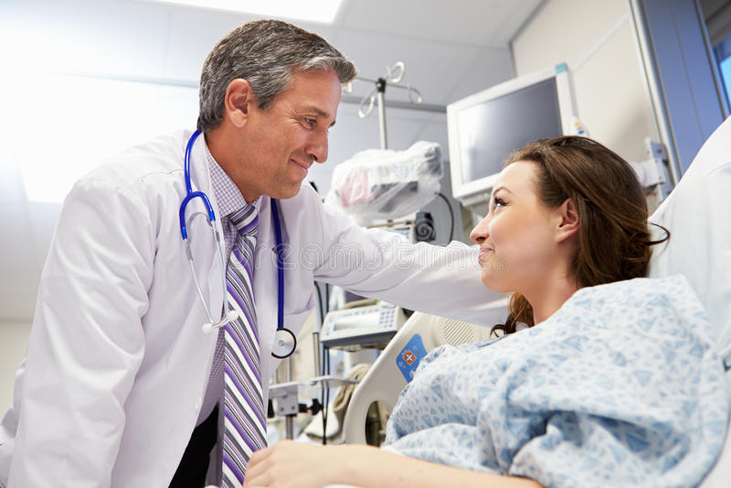 女性耐心谈话与男性In医生急诊室 库存图片