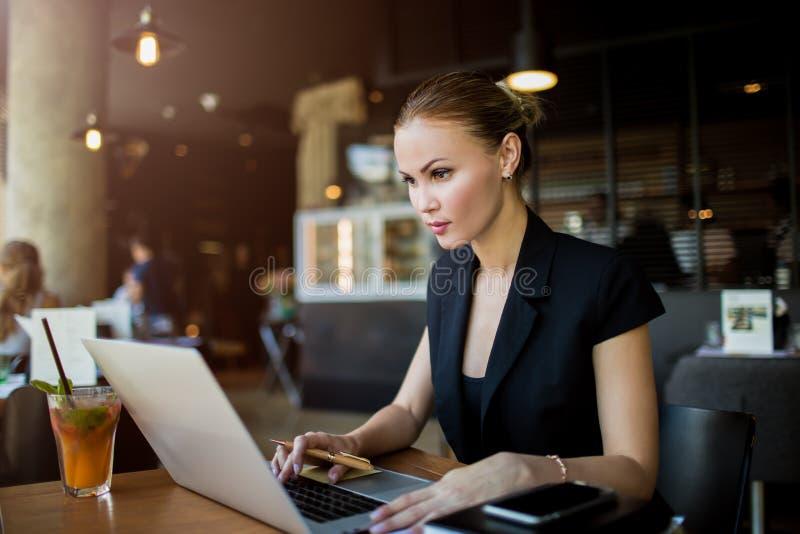 女性职业经纪人通过便携式电脑设备查看电子邮件 免版税库存照片