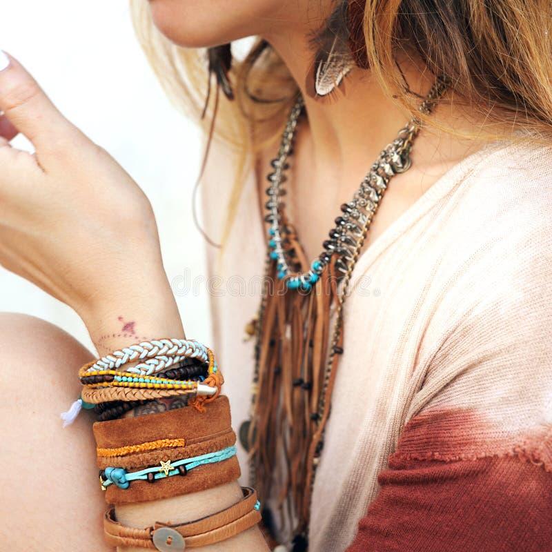 女性脖子和手有许多boho镯子、皮革项链和耳环的有羽毛的 免版税图库摄影