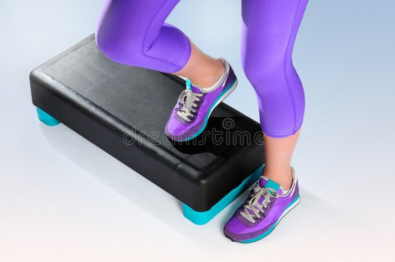 女性脚在健身有氧步进行使 免版税图库摄影