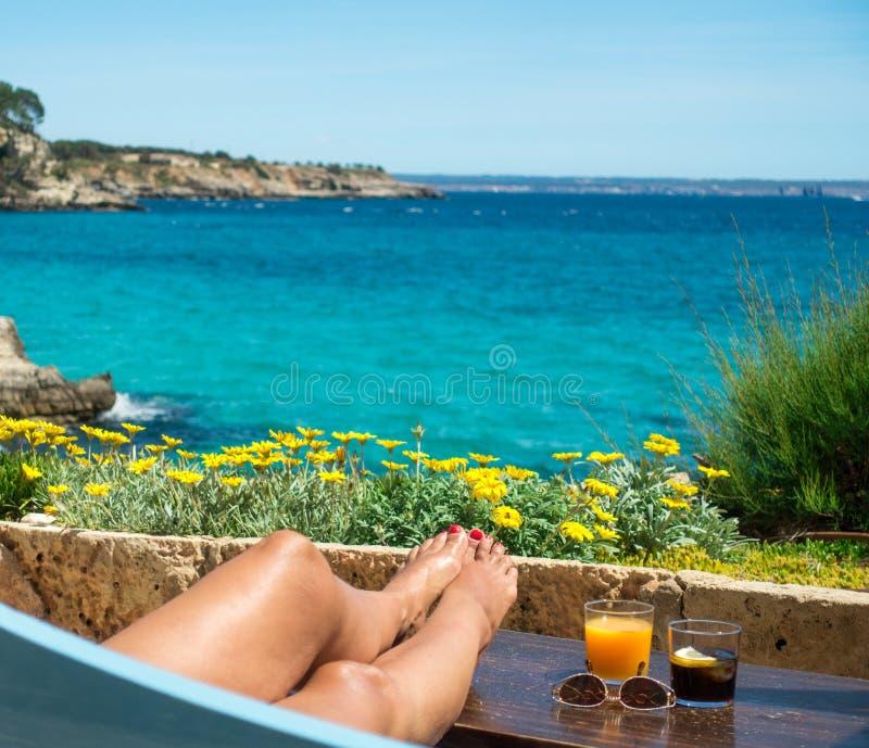 女性腿和鸡尾酒反对热带海和花 免版税库存照片