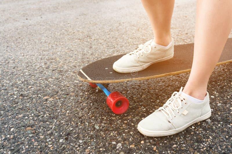 女性腿特写镜头在旧布运动鞋的在沥青背景的一longboard在日落的 与女孩的大滑板 库存照片
