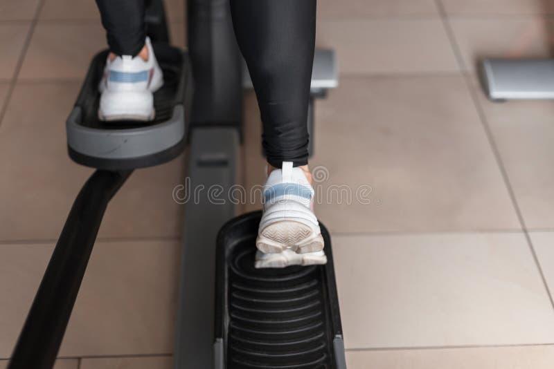 女性腿特写镜头在白色体育运动鞋的在健身房的一台现代步进模拟器 女孩做锻炼体育类 库存照片
