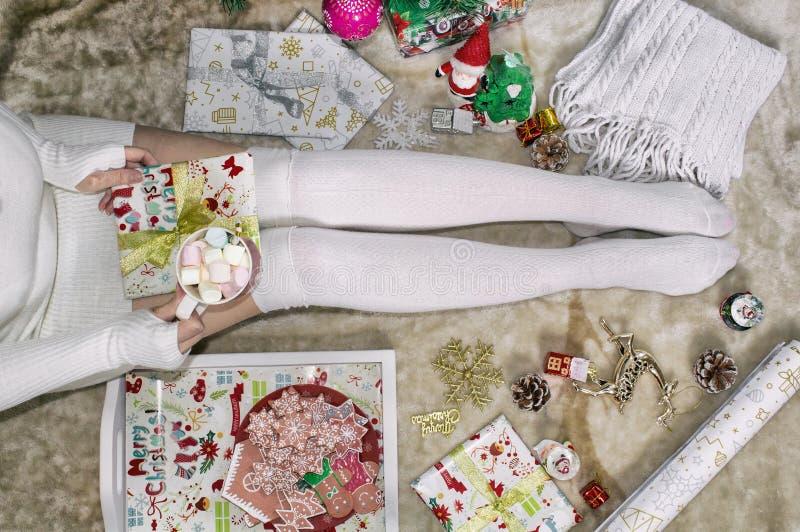 女性腿,女孩拿着一个杯子蛋白软糖 特写镜头 球圣诞节查出的心情三白色 免版税库存照片