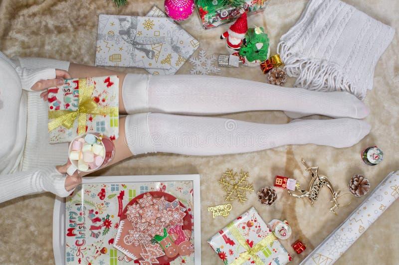 女性腿,女孩拿着一个杯子蛋白软糖 特写镜头 球圣诞节查出的心情三白色 库存图片