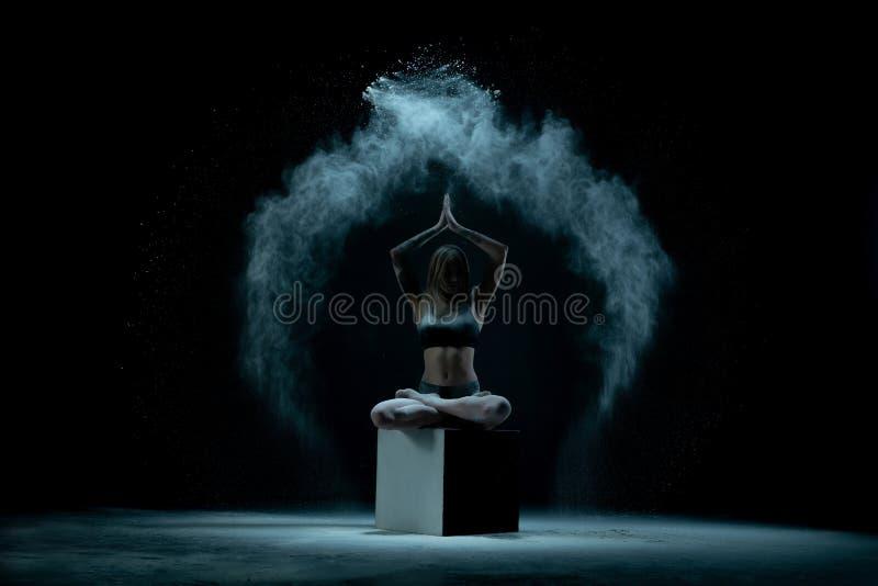 女性舞蹈家盘着腿坐黑暗的阶段 免版税库存照片