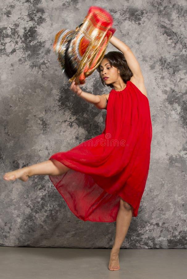 女性舞蹈家踢,穿一件红色礼服,灰色背景 免版税库存照片