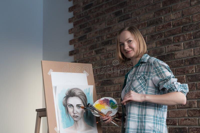 女性艺术家在屋子里画 免版税库存照片