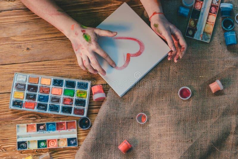 年轻女性艺术家绘画图片在演播室 免版税库存照片