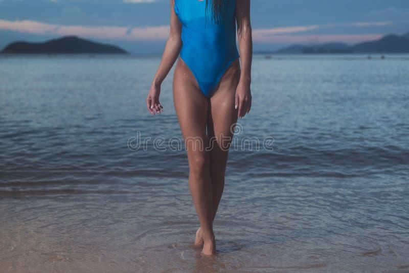 女性苗条腿和身体特写镜头在站立在海滩的蓝色泳装在晚上与海在背景中 库存图片