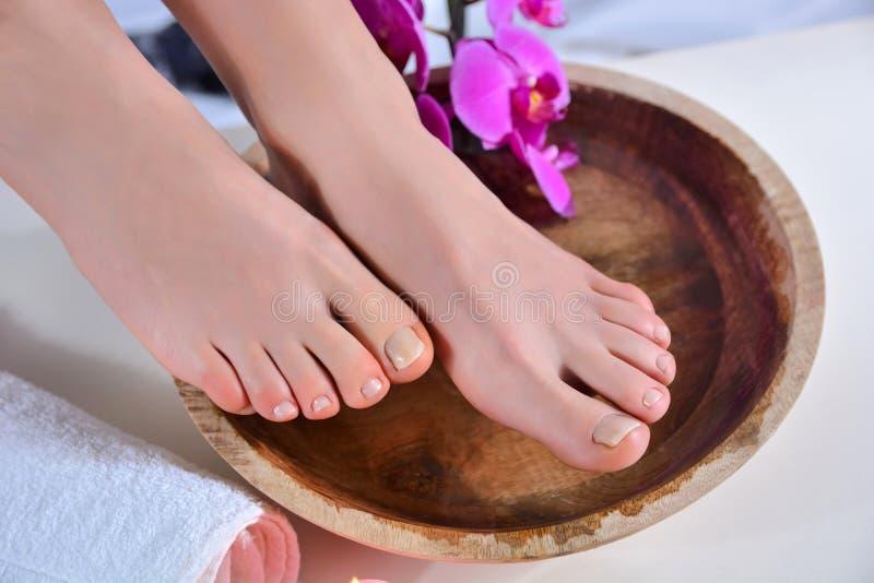 女性裸脚在木碗上,有水和兰花的花石。 免版税库存图片