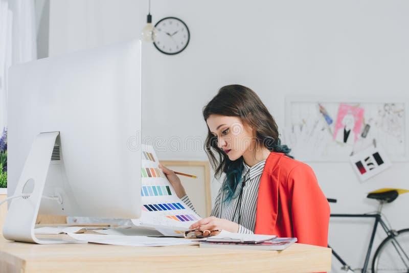 女性设计师与调色板一起使用在工作表旁边 库存图片