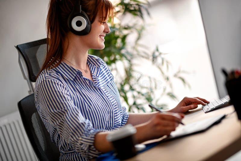 女性设计师听的音乐,当研究计算机时 免版税库存图片