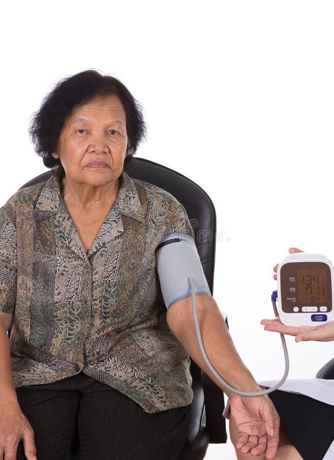女性资深妇女医生测量的血压  图库摄影
