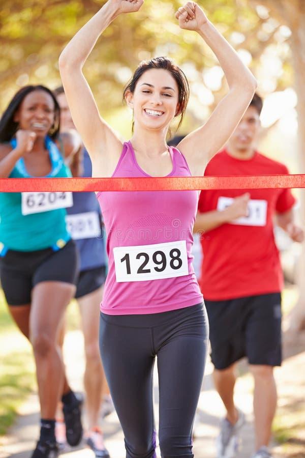 女性赛跑者赢取的马拉松 免版税库存图片