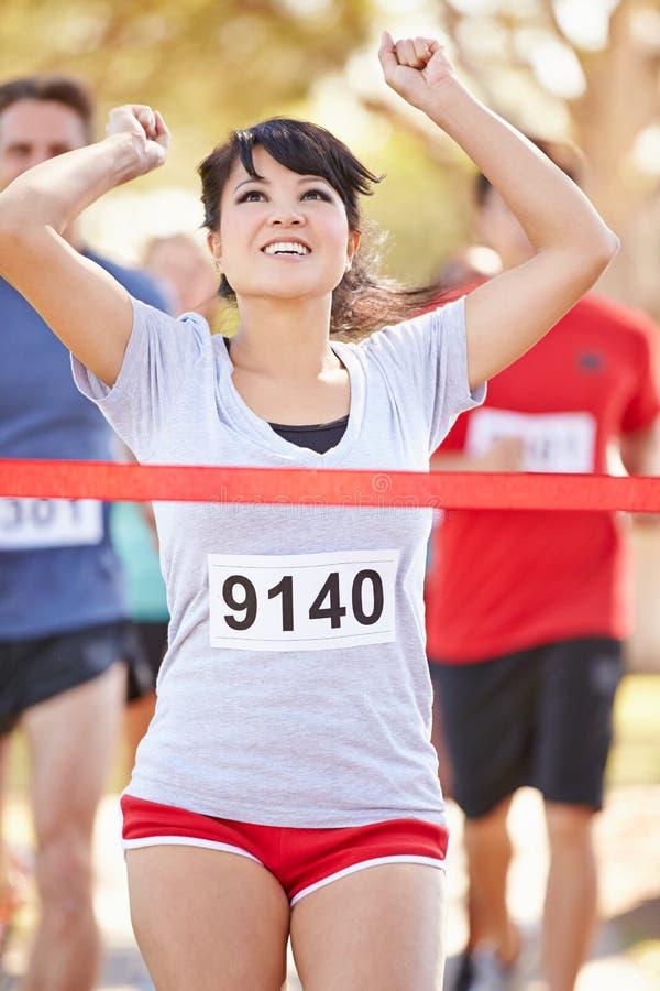 女性赛跑者赢取的马拉松 免版税图库摄影