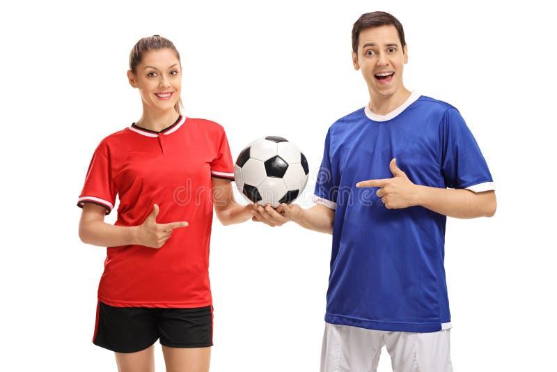 女性足球运动员和一男性足球运动员指向 免版税库存图片