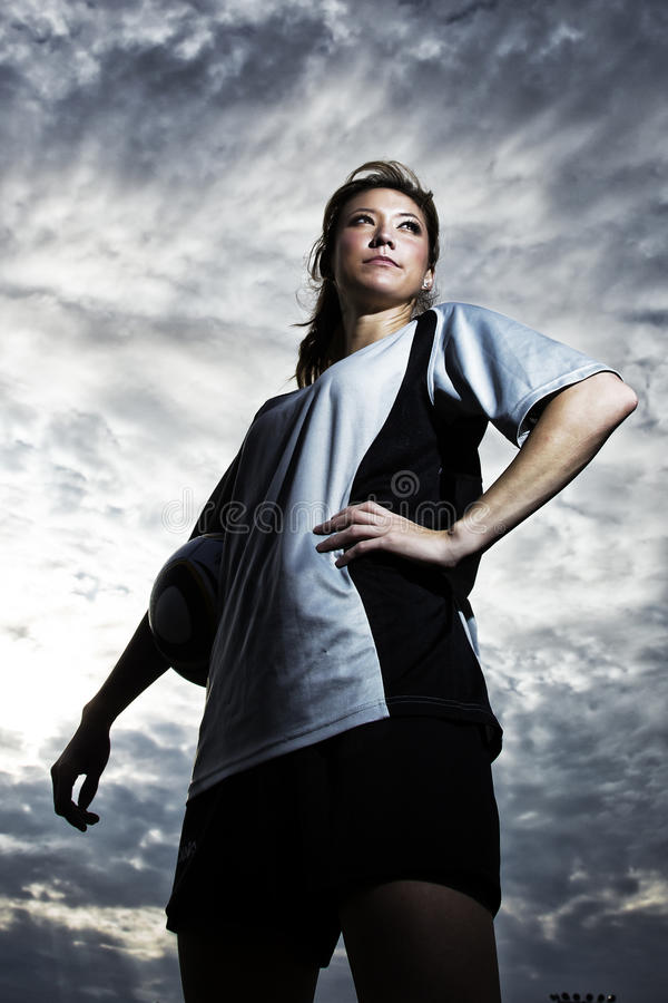女性足球运动员被摆在 免版税库存图片