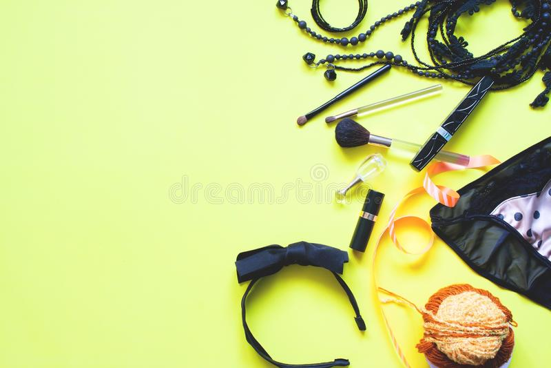 女性辅助部件平的位置在黑和金黄概念在黄色背景,春天时尚概念的 库存照片