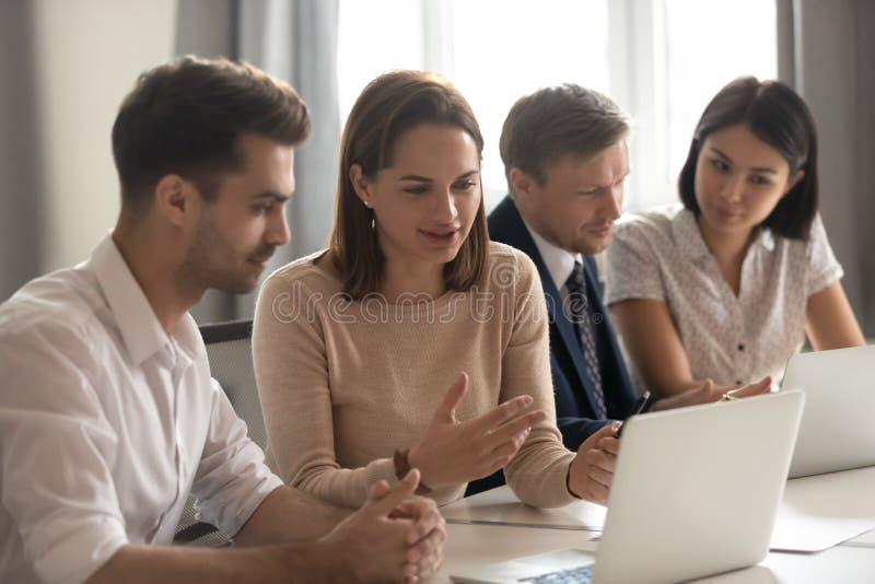 女性辅导者帮助男性实习生解释在膝上型计算机的网上战略 免版税库存照片