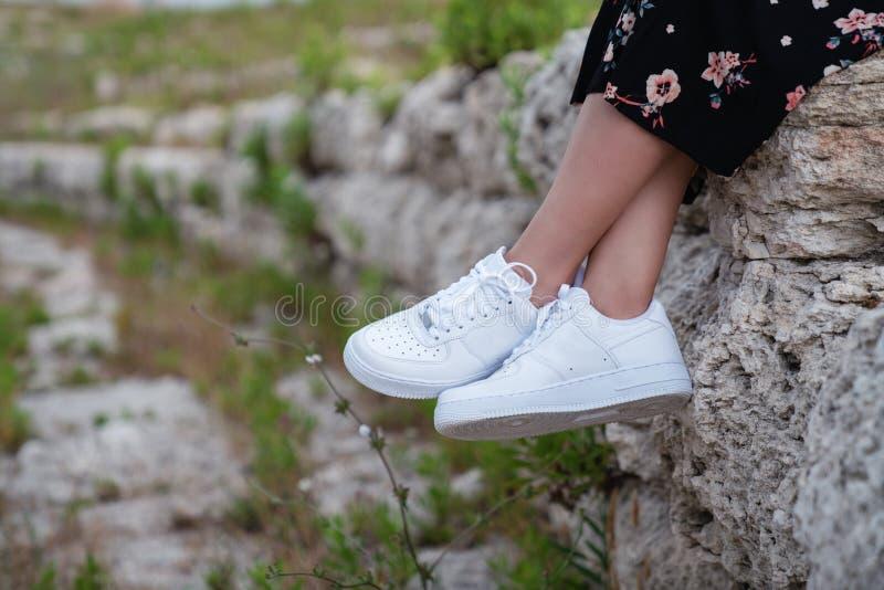 女性运动鞋 在脚的白色女性鞋子 运动鞋特写镜头 库存照片