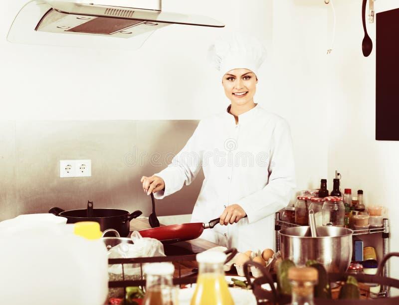 女性运转在厨房的厨师佩带的制服 图库摄影