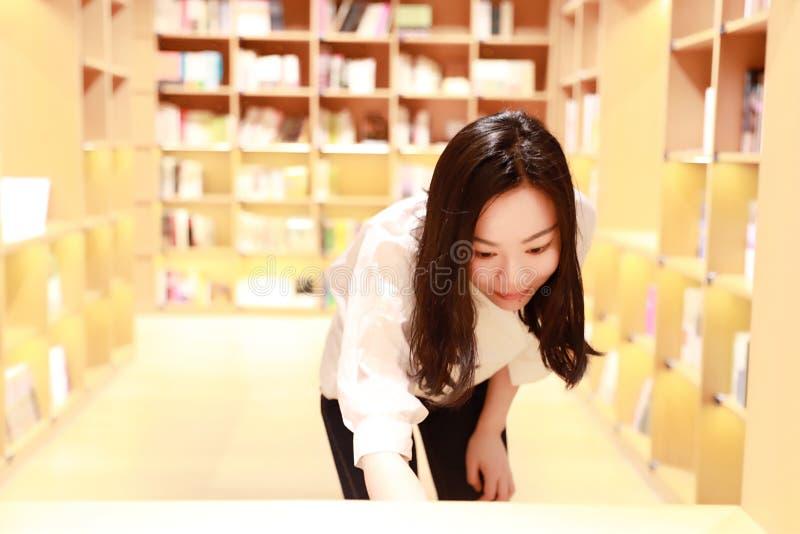 女性运载一个小红色袋子的一名美丽的相当女孩妇女在她选择采撷选择书的书店图书馆读了书 库存照片