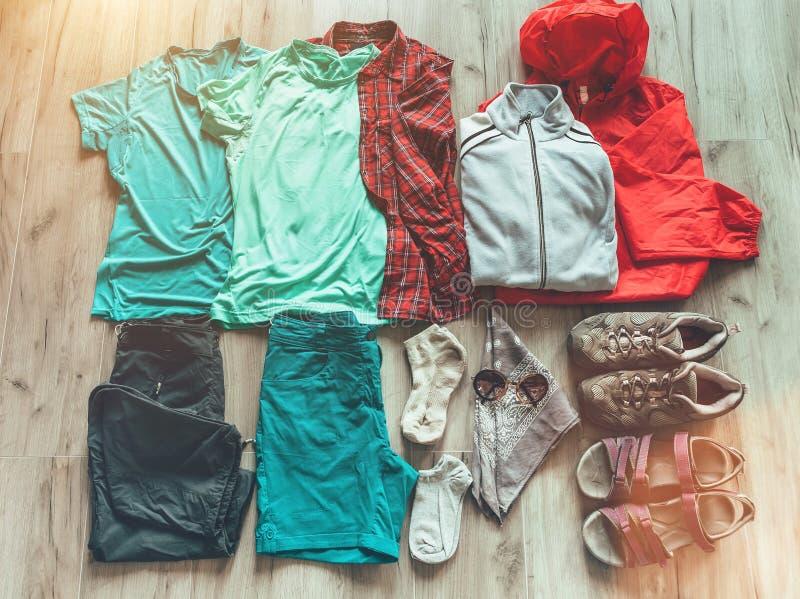 女性远足的集合必要的衣裳:短裤,裤子,迁徙的袜子,热量上面,T恤杉,羊毛夹克,起动,凉鞋 库存图片
