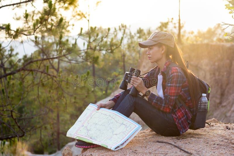 女性远足者看一看在地图并且使用双筒望远镜 免版税库存照片