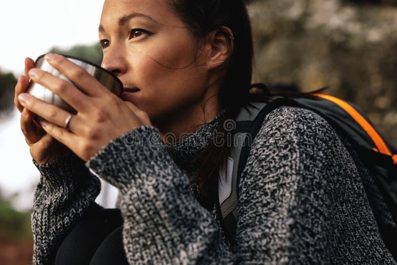 年轻女性远足者饮用的咖啡 库存照片