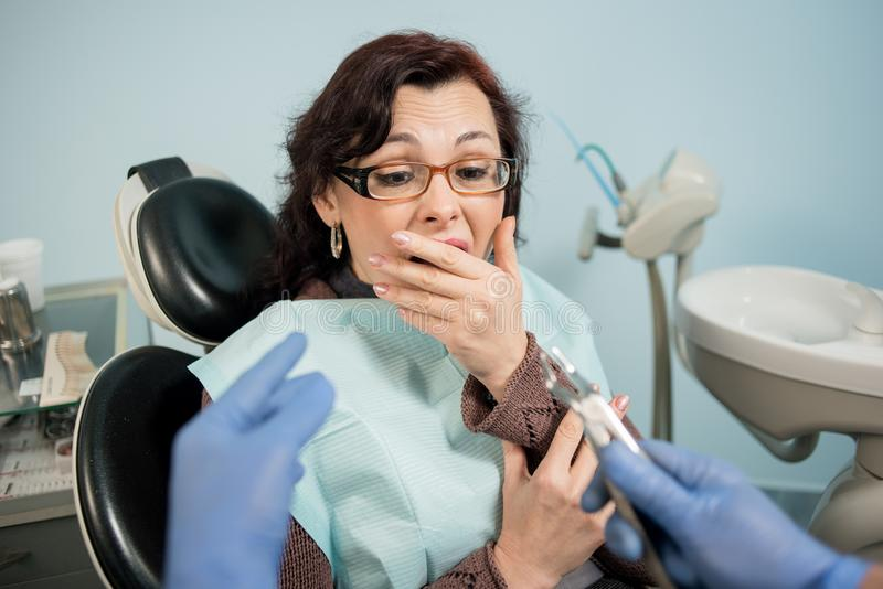 女性通过牙医和盖她的嘴吓唬了用手在牙齿诊所的牙医任命 免版税库存照片