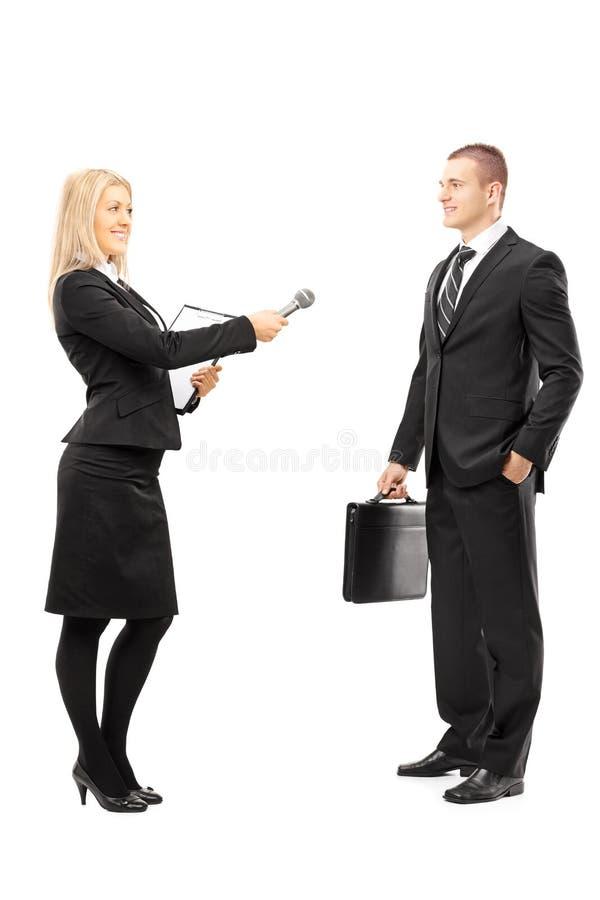 年轻女性采访者谈话与男性商人 免版税库存图片