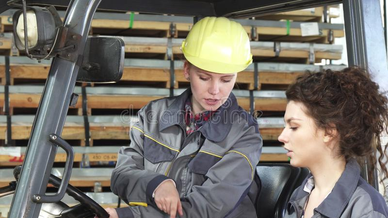 女性铲车操作员谈话与她的同事,当工作时 库存图片