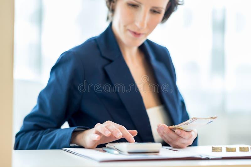 年轻女性银行工作人员在工作 免版税库存照片