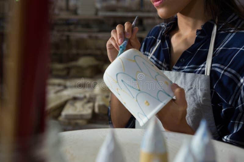 女性陶瓷工绘画杯子的中间部分 库存图片