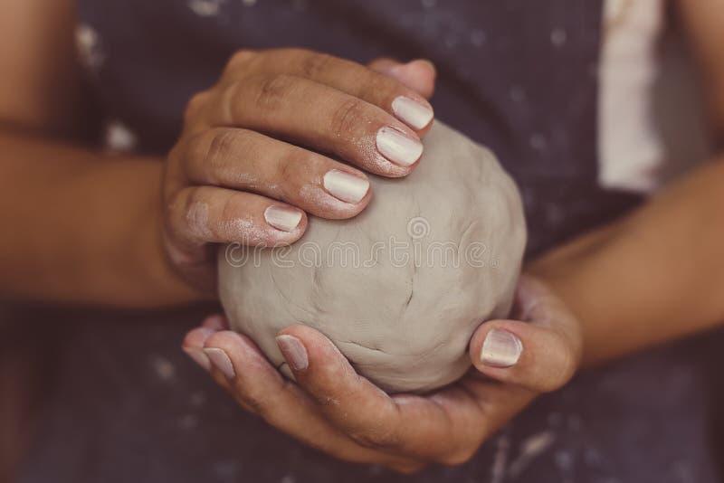 女性陶瓷工递拿着瓦器的,选择聚焦黏土 免版税图库摄影