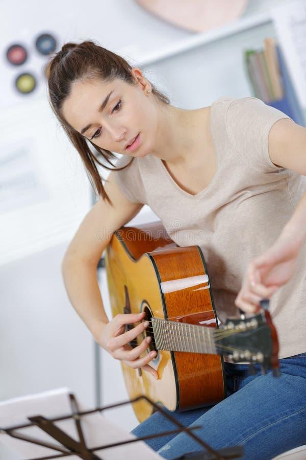 女性青少年的使用的吉他在家 库存照片
