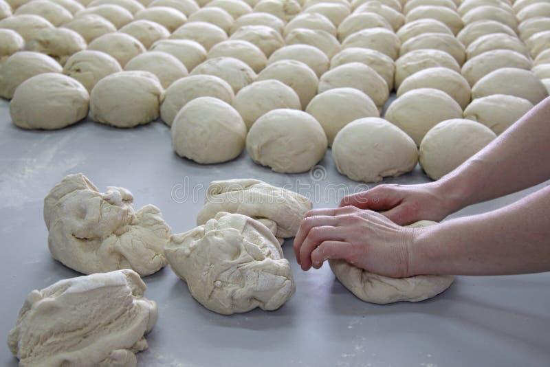 女性面包师揉的面团 免版税库存照片