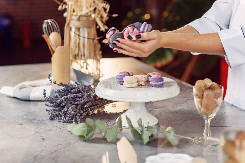 女性面包师的手的关闭有拿着colorf的黑修指甲的 免版税图库摄影