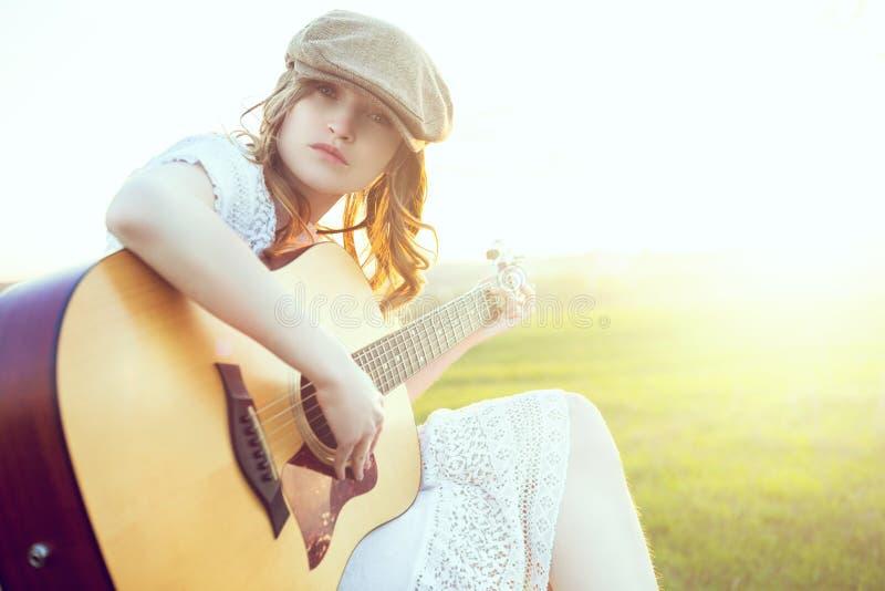 女性音乐家坐弹声学吉他和唱歌曲的绿草 放松在绿色春天或夏天的有天才的女孩 免版税库存图片