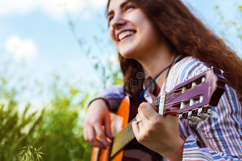 女性音乐家坐绿草侧视图 库存图片