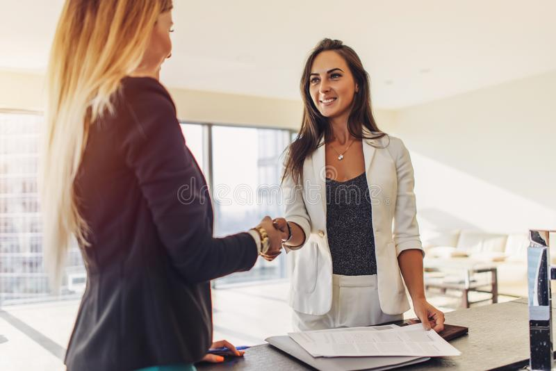 女性顾客与同意的房地产开发商握手签站立在新的现代单室公寓的合同 图库摄影