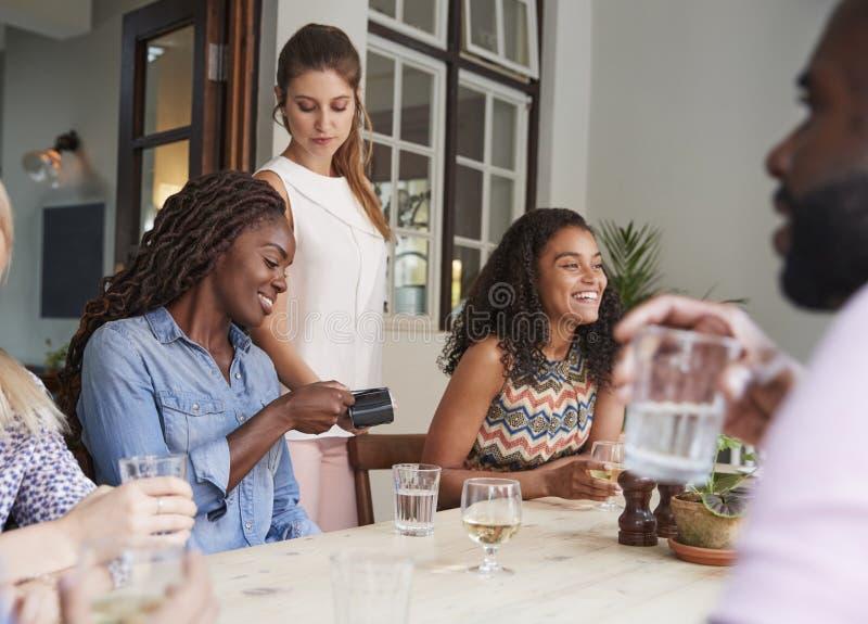 女性顾客在餐馆使用不接触的信用卡终端的付帐 图库摄影