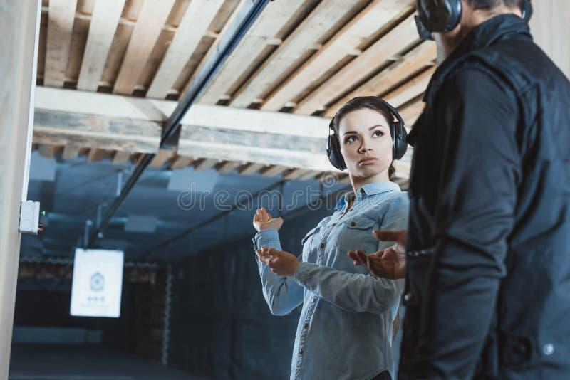 女性顾客谈话与射击的男性辅导员 库存照片