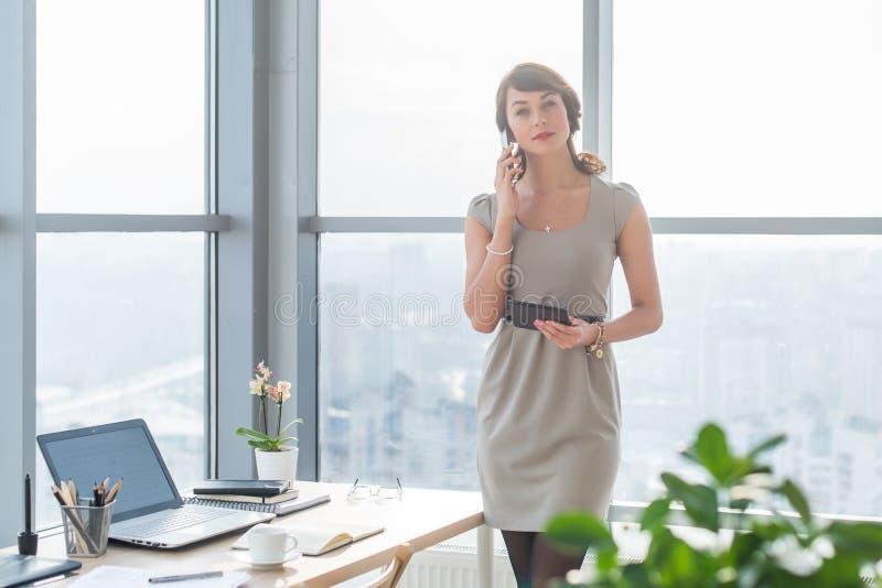 年轻女性顾问有企业电话在办公室在她的工作场所 秘书说在巧妙的电话里,举行 库存图片