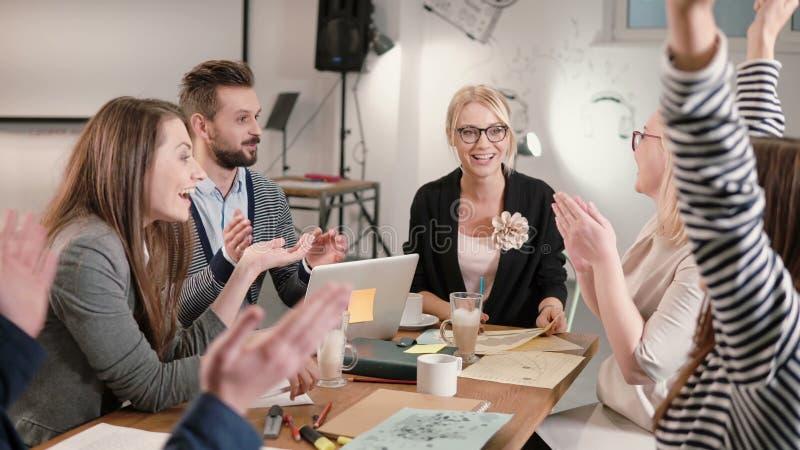 女性领导在一个现代起始的办公室报告了好消息,大家是愉快的,高fiving企业队 库存图片