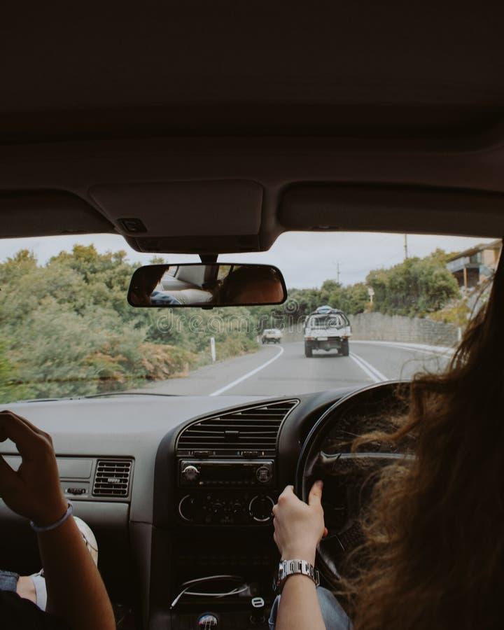 女性驾驶有她的从里边坐在她的射击旁边的朋友的一辆汽车 免版税库存图片